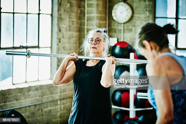 Senior woman doing barbell lifts during workout