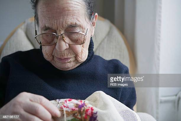 Senior woman doing cross stitch