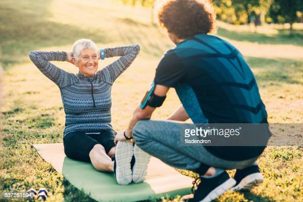 Senior woman doing crunches with a personal trainer