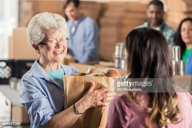 A senior woman donates bag of groceries to food bank