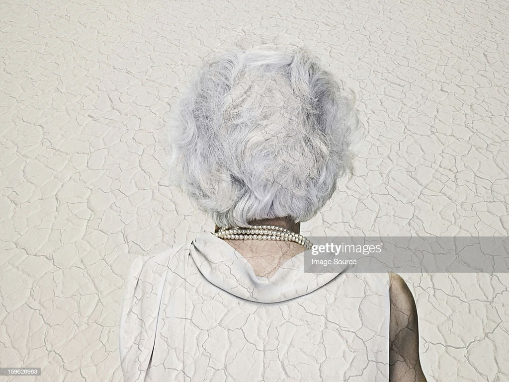 Senior woman double exposed with an arid landscape : Stock Photo