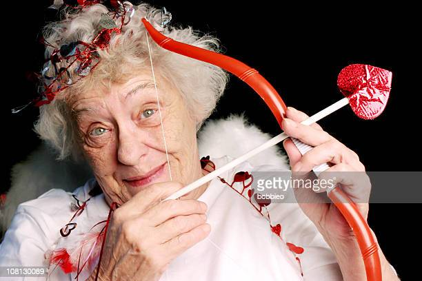 Senior Woman Dressed as Cupid with Bow and Arrow