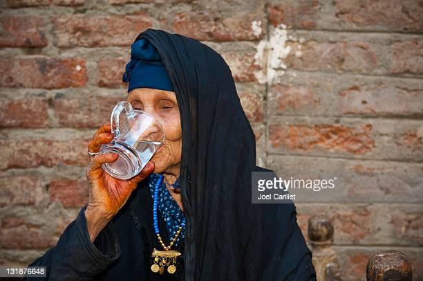 Senior femme boire de l'eau pure en Égypte
