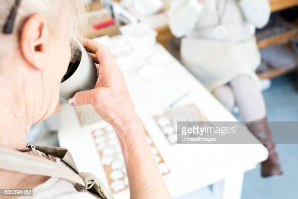 Senior woman drinking coffee in her workshop