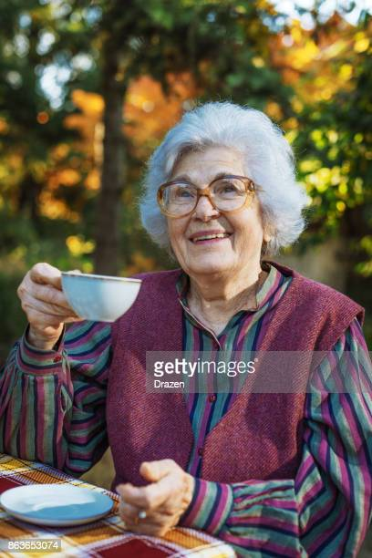 Senior woman drinking coffee in the garden