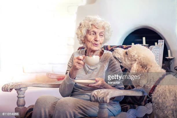 Senior woman drinking morning coffee and talking with dog