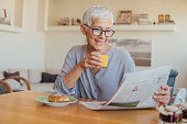 Elderly woman holding newspapers while having breakfast at home