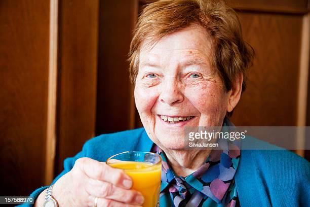 senior donna bere succo d'arancia