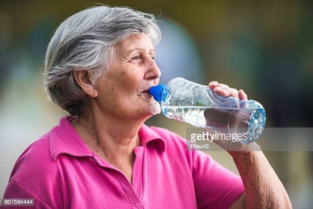 Senior woman drinking refreshing water from a bottle.