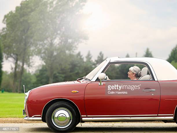 Senior woman driving along in red convertible