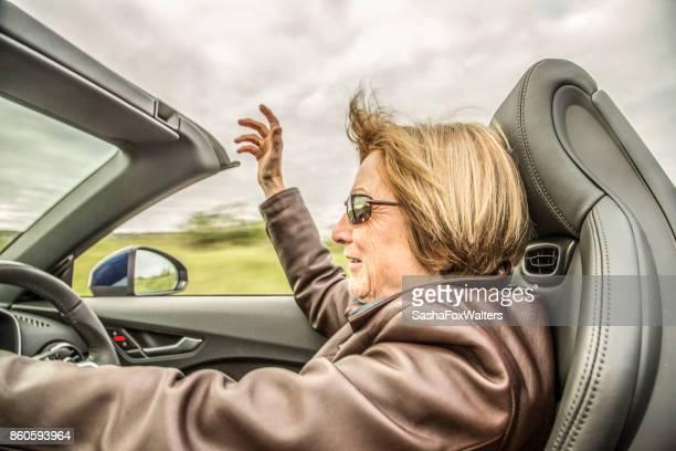 Senior woman driving convertible