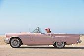Senior woman driving pink convertible