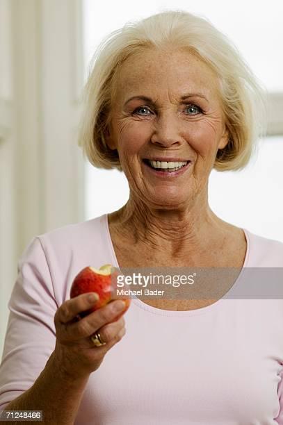Senior woman eating apple, smiling, close-up, portrait