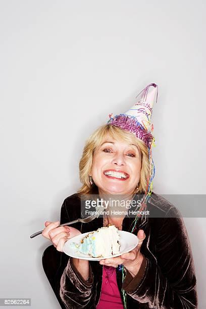 Senior woman eating birthday cake