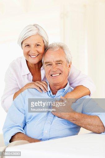 Senior donna abbracciare uomo da dietro al tavolo da pranzo