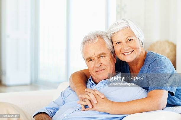 Senior donna abbracciare uomo da dietro a casa