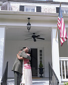 Senior woman embracing son in military uniform on porch, side view