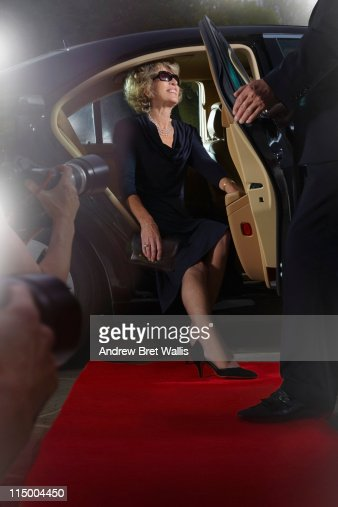 Senior woman emerging from limousine to paparazzi : Stock Photo