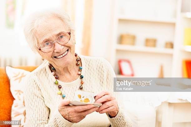 Senior Frau genießen eine Tasse Kaffee wie zu Hause fühlen