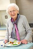 Senior woman enjoying meal in kitchen smiling
