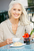 Senior Woman Enjoying Snack At Outdoor Cafe Smiling To Camera