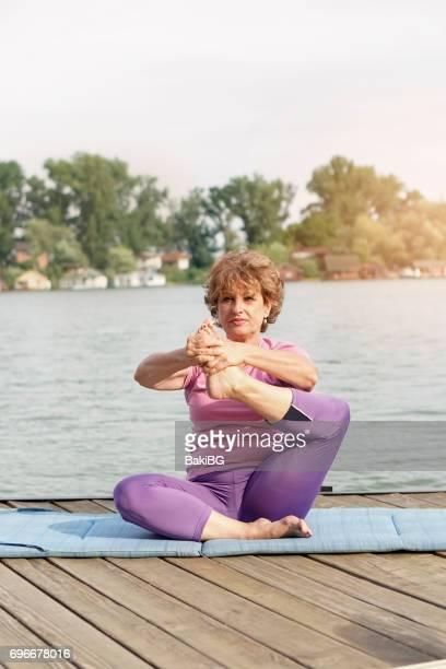 Senior woman exercising beside the river