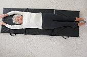 Senior woman exercising on a floor mat