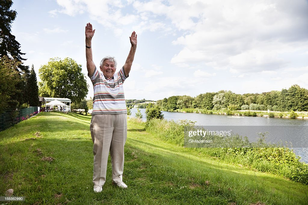 senior woman exercising outdoors in summer