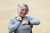 An African American senior woman, in her 60s, exercising outdoors in the park.  She is checking her pulse to see if her exercise has increased her heart rate.  She is smiling, with two fingers on her