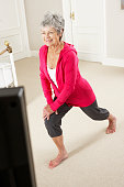 Senior Woman Exercising Whilst Watching Fitness DVD On Television In Bedroom.
