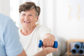Happy senior woman exercising arms with small weights with help from a physiotherapist and copy space