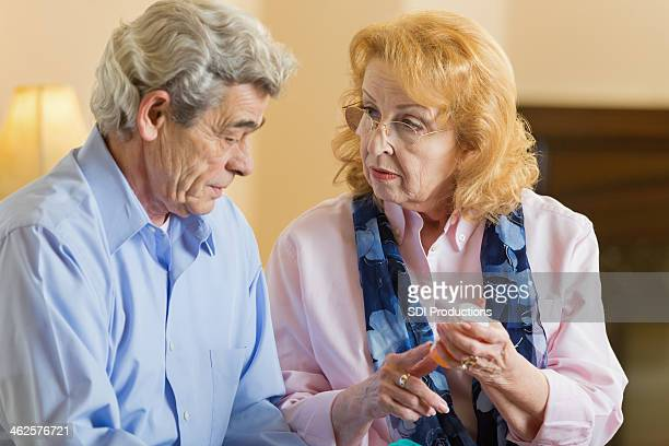 Senior woman explaining prescription medication dosage to husband