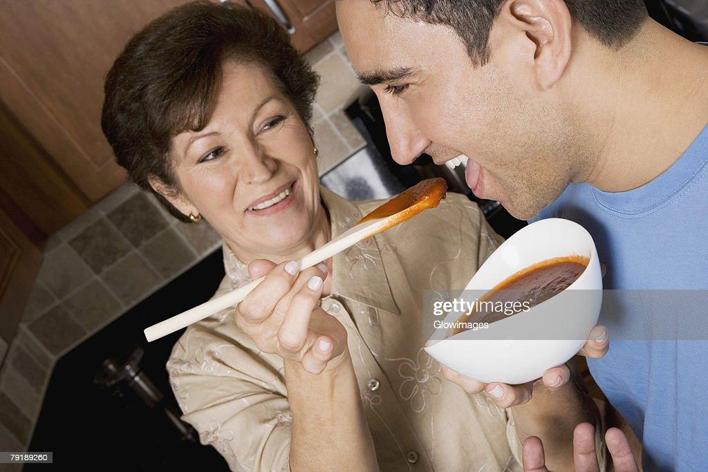 Senior woman feeding tomato soup to her son in the kitchen : Foto de stock