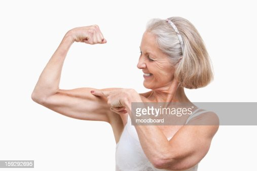 Senior woman flexing muscles against white background : Stock Photo