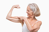Senior woman flexing muscles against white background