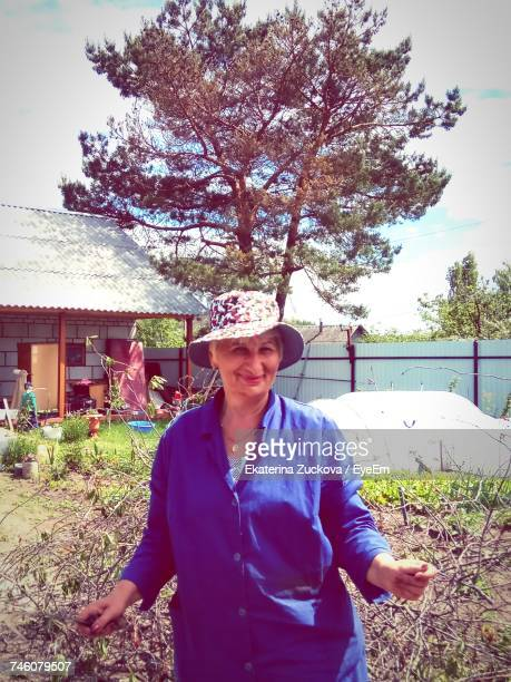 Senior Woman Gardening In Yard On Sunny Day