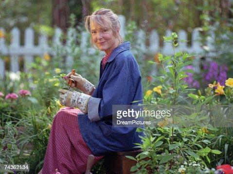 Senior woman gardening, smiling, portrait, side view : Stock Photo