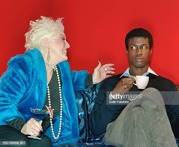 Senior woman gesturing to young man relaxing on sofa
