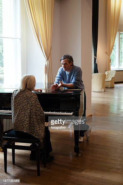 senior woman gets a music lesson at a grand piano