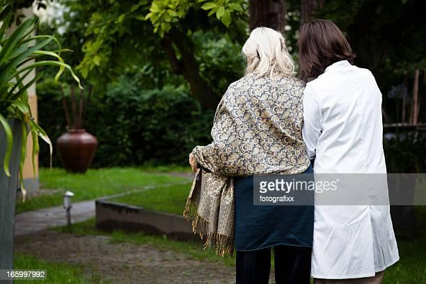 Femme senior joue à l'aide de l'infirmière pour marcher