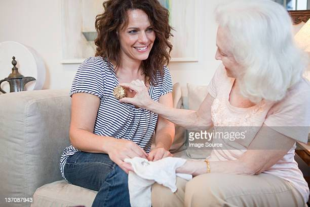 Senior woman giving daughter a brooch