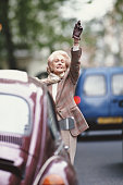 Senior woman hailing taxi on street