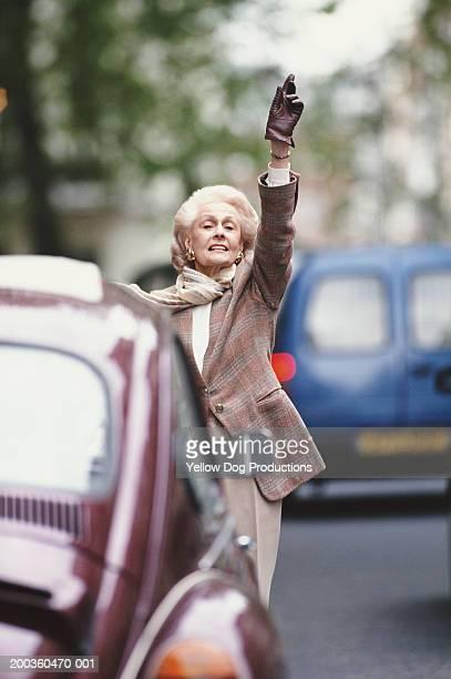Senior woman hailing taxi on street