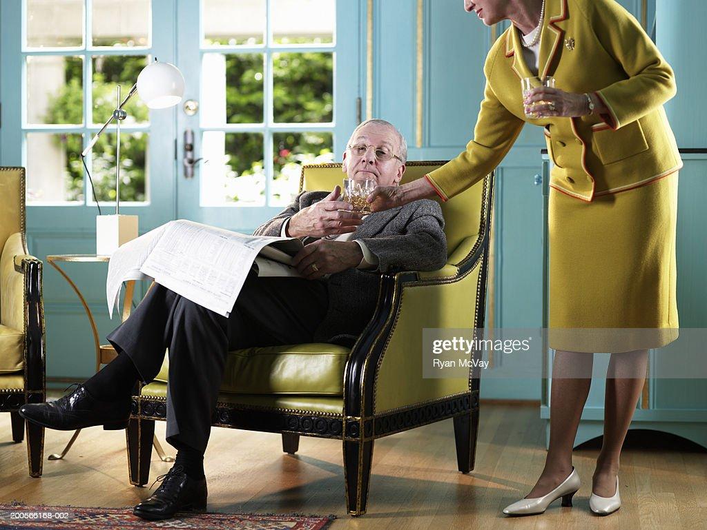 Senior woman handing drink to senior man sitting in armchair : Stock Photo