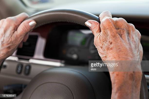 senior woman hands, driving car, steering wheel