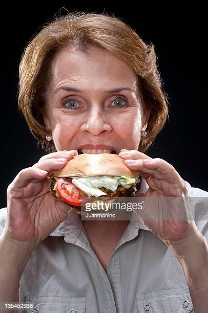 Femme âgée ayant un hamburger