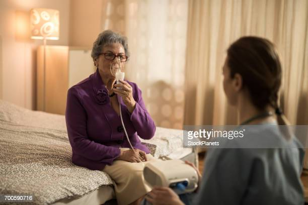 Senior woman having a medical therapy with oxygen at home.