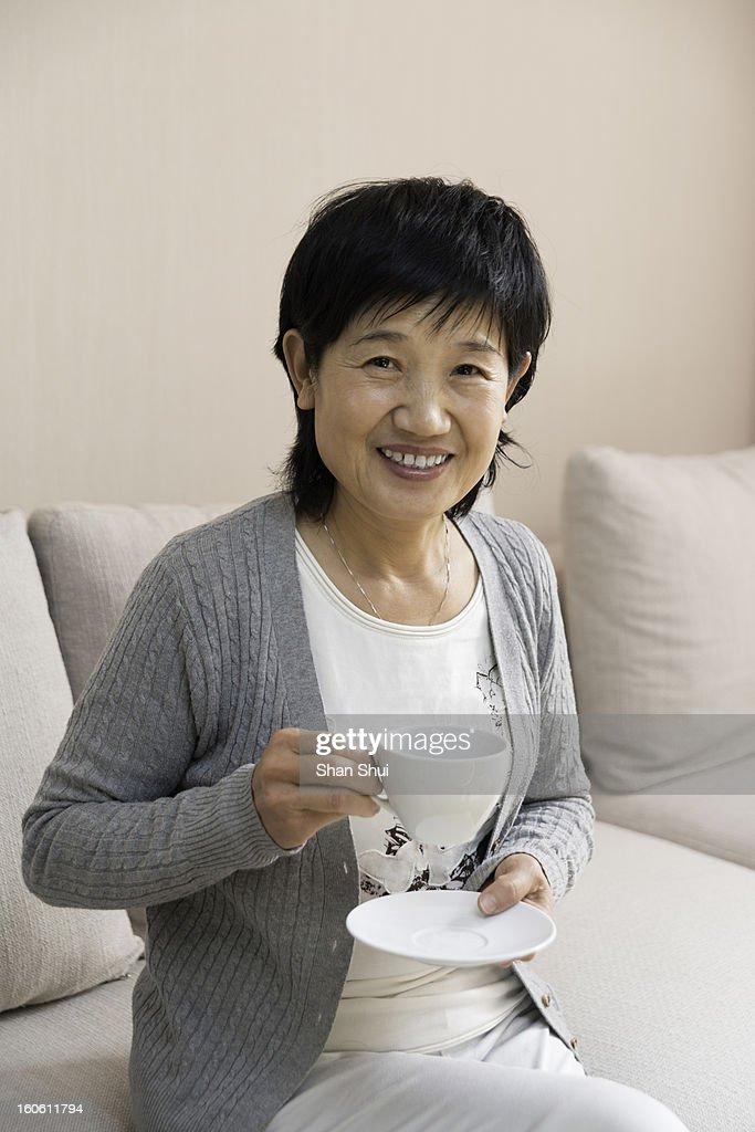Senior woman having coffee at home : Stock Photo
