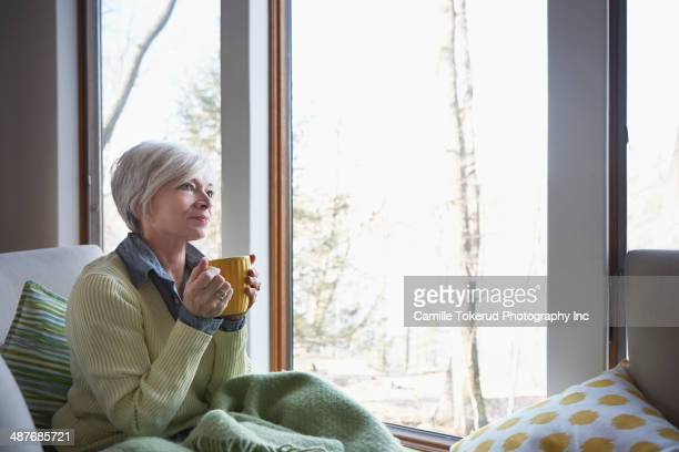 Senior woman having cup of coffee on sofa