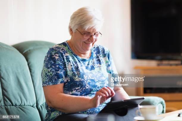 Senior woman having fun with digital tablet